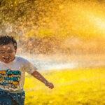 A boy running through spray of water.